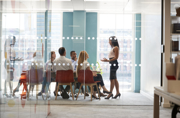 Female boss talking in front of her team inside the meeting room