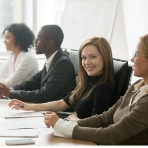 Smiling businesswoman looking at camera at corporate group meeting