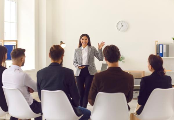 Team leader greeting workers in corporate meeting