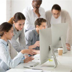 Woman teaching employees using a desktop