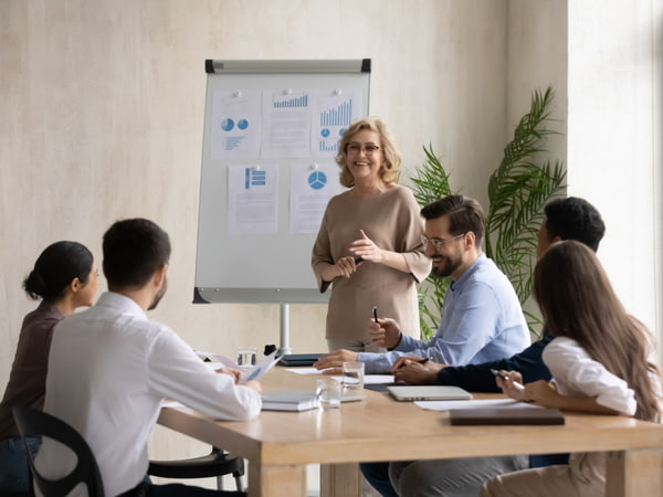 Mature businesswoman presenting business project to coworkers