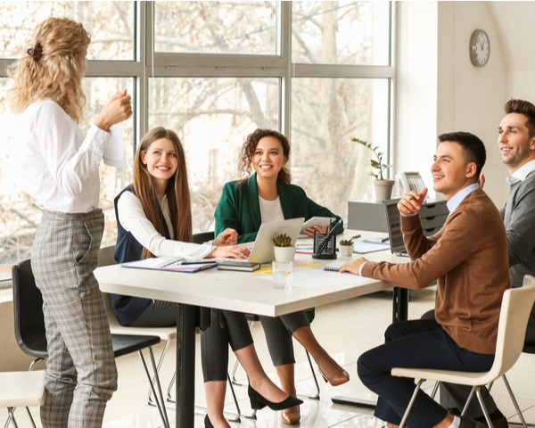 Female team leader teaching young people in office