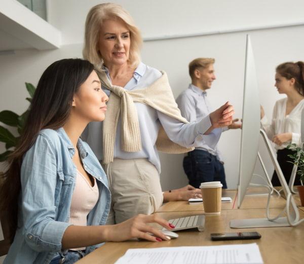 Senior friendly executive teaching new employee