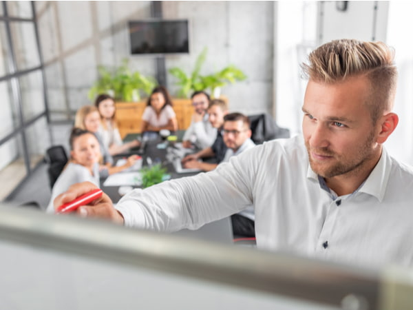 Team leader teaches employees at a business meeting in a conference room