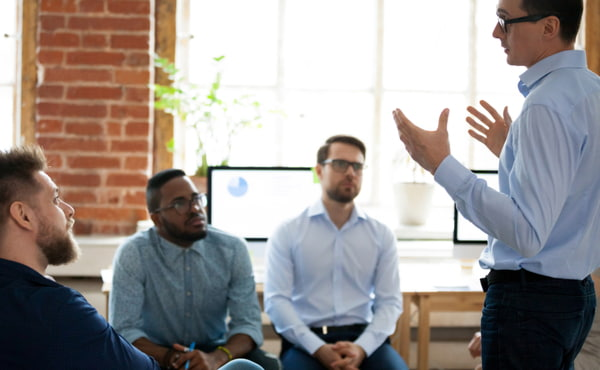 Confident male leader speaking at diverse team meeting