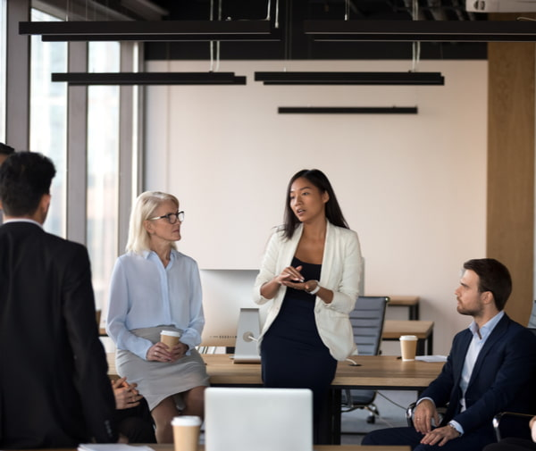 Team leader speaking at diverse corporate group meeting