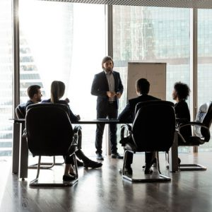 Confident team leader giving flip chart presentation at corporate meeting
