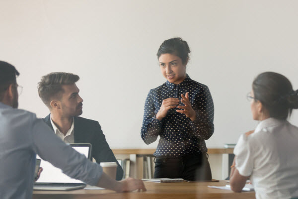 Woman discussing in front of her colleagues