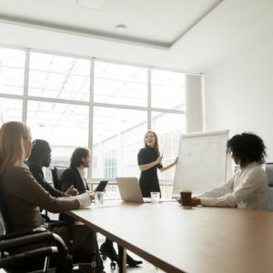 Businesswoman giving presentation to diverse partners in meeting room