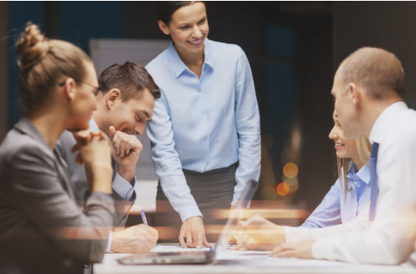 Smiling female boss talking to business team
