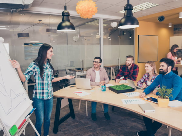 Young woman near whiteboard making presentation about growth of company
